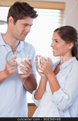 Portrait of a happy couple drinking coffee stock photo, Portrait of a happy couple drinking coffee in their kitchen by Wavebreak Media