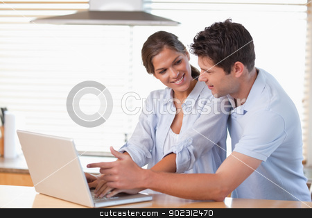 Happy couple using a laptop stock photo, Happy couple using a laptop in their kitchen by Wavebreak Media
