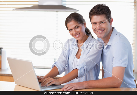 Smiling couple using a laptop stock photo, Smiling couple using a laptop in their kitchen by Wavebreak Media