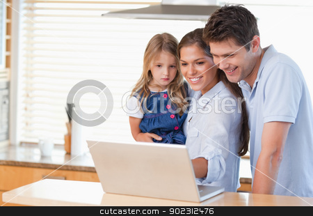 Family using a laptop stock photo, Family using a laptop in a kitchen by Wavebreak Media