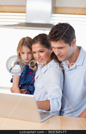 Portrait of a family using a laptop stock photo, Portrait of a family using a laptop in their kitchen by Wavebreak Media