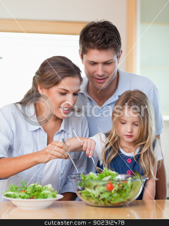 Portrait of a family preparing a salad stock photo, Portrait of a family preparing a salad in their kitchen by Wavebreak Media