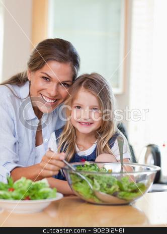 Portrait of a mother and her daughter preparing a salad stock photo, Portrait of a mother and her daughter preparing a salad in their kitchen by Wavebreak Media