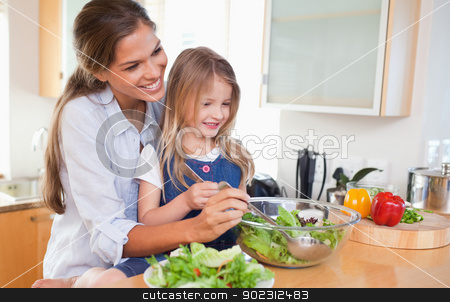 Mother and her daughter preparing a salad stock photo, Mother and her daughter preparing a salad in their kitchen by Wavebreak Media