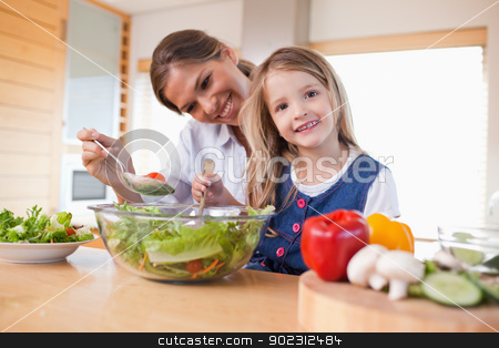 Happy mother and her daughter preparing a salad stock photo, Happy mother and her daughter preparing a salad in their kitchen by Wavebreak Media