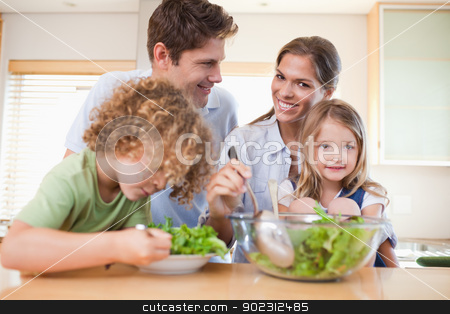 Happy family preparing a salad stock photo, Happy family preparing a salad in their kitchen by Wavebreak Media
