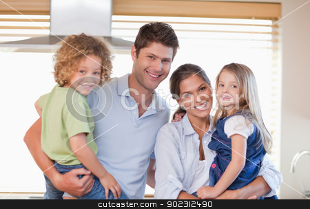 Smiling family posing stock photo, Smiling family posing in their kitchen by Wavebreak Media