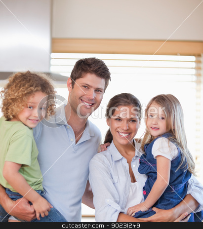 Smiling family standing up stock photo, Smiling family standing up in their kitchen by Wavebreak Media