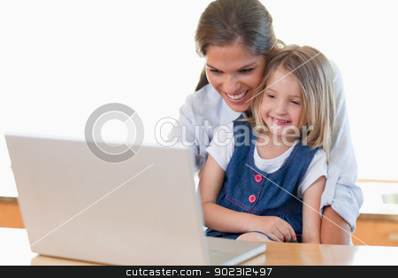 Mother and her daughter using a notebook stock photo, Mother and her daughter using a notebook in their kitchen by Wavebreak Media