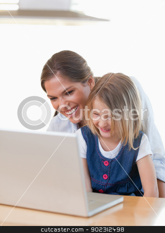 Portrait of a mother and her daughter using a notebook stock photo, Portrait of a mother and her daughter using a notebook in their kitchen by Wavebreak Media