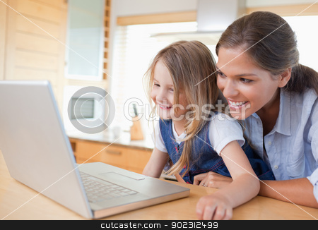 Smiling mother and her daughter using a notebook stock photo, Smiling mother and her daughter using a notebook in their kitchen by Wavebreak Media