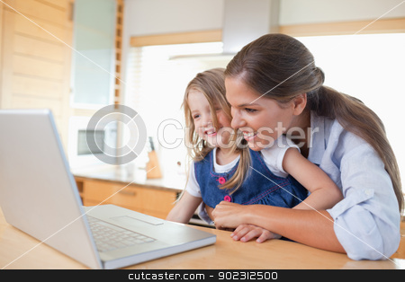 Smiling mother and her daughter using a laptop stock photo, Smiling mother and her daughter using a laptop in their kitchen by Wavebreak Media