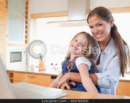 Happy mother and her daughter using a laptop stock photo, Happy mother and her daughter using a laptop in their kitchen by Wavebreak Media