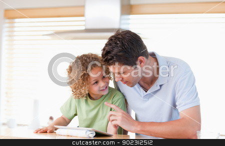 Young boy and his father using a tablet computer stock photo, Young boy and his father using a tablet computer in their kitchen by Wavebreak Media