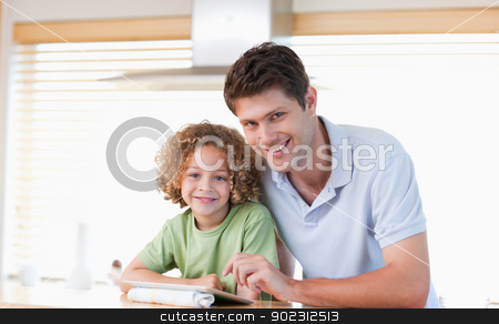 Smiling boy and his father using a tablet computer stock photo, Smiling boy and his father using a tablet computer in their kitchen by Wavebreak Media
