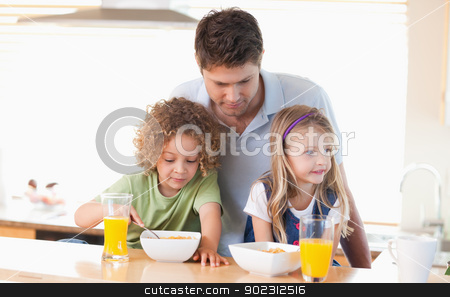 Young father with his children having breakfast stock photo, Young father with his children having breakfast in their kitchen by Wavebreak Media