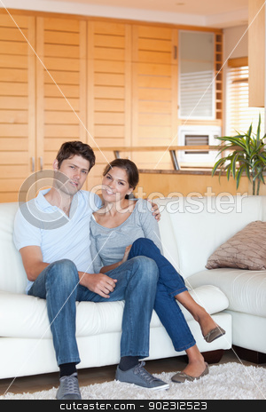 Portrait of a couple sitting on a couch stock photo, Portrait of a couple sitting on a couch while looking at the camera by Wavebreak Media