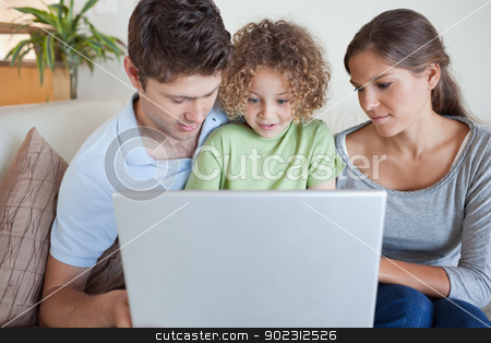 Family using a laptop stock photo, Family using a laptop while sitting on a sofa by Wavebreak Media
