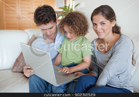 Young family using a laptop stock photo, Young family using a laptop in their living room by Wavebreak Media