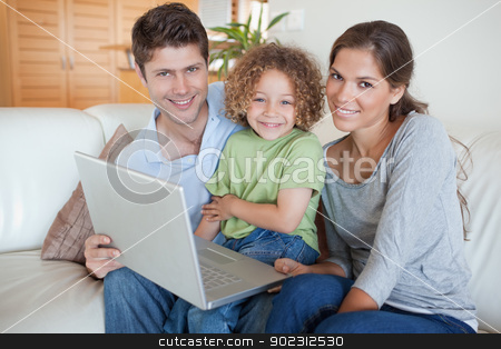 Happy family using a laptop stock photo, Happy family using a laptop in their living room by Wavebreak Media