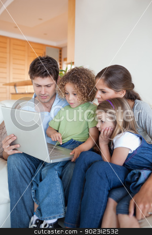 Portrait of a family using a notebook stock photo, Portrait of a family using a notebook in their living room by Wavebreak Media