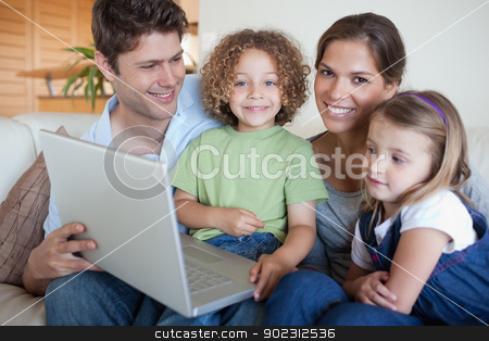 Smiling family using a laptop stock photo, Smiling family using a laptop in their living room by Wavebreak Media