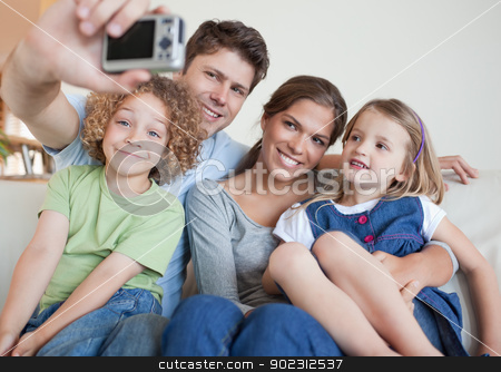 Family taking a photo of themselves stock photo, Family taking a photo of themselves in their living room by Wavebreak Media