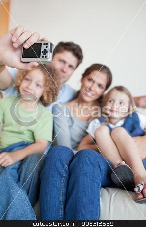 Portrait of a happy family taking a photo of themselves stock photo, Portrait of a happy family taking a photo of themselves in their living room by Wavebreak Media