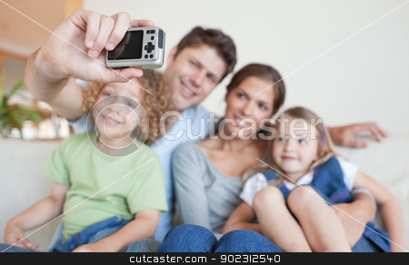 Happy family taking a photo of themselves stock photo, Happy family taking a photo of themselves in their living room by Wavebreak Media