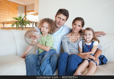Family watching TV together stock photo, Family watching TV together in their living room by Wavebreak Media