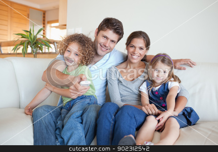 Happy family watching TV together stock photo, Happy family watching TV together in their living room by Wavebreak Media