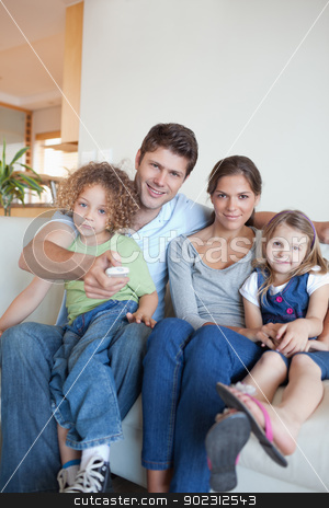 Portrait of a family watching TV together stock photo, Portrait of a family watching TV together in their living room by Wavebreak Media