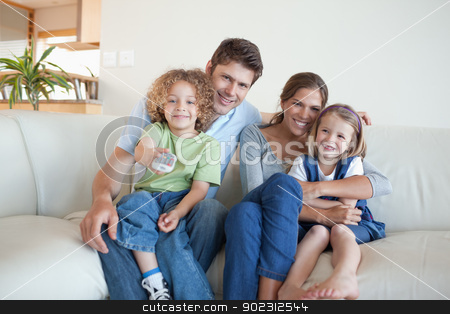 Smiling family watching TV together stock photo, Smiling family watching TV together in their living room by Wavebreak Media