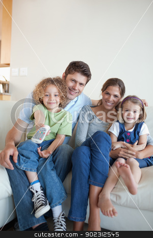 Portrait of a happy family watching TV together stock photo, Portrait of a happy family watching TV together in their living room by Wavebreak Media