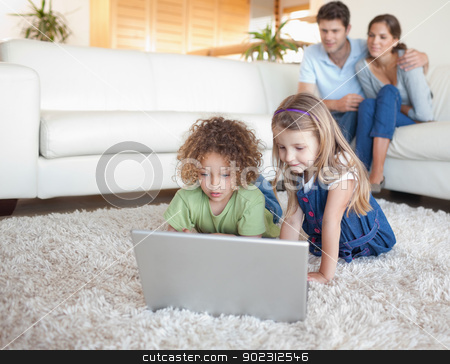 Children using a notebook while their parents are watching stock photo, Children using a notebook while their parents are watching in their living room by Wavebreak Media