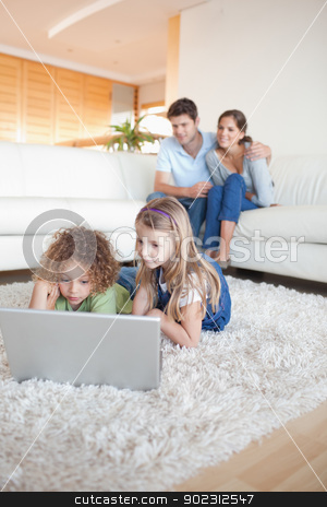 Portrait of children using a notebook while their parents are wa stock photo, Portrait of children using a notebook while their parents are watching in their living room by Wavebreak Media