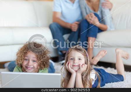 Cute children using a laptop while their parents are watching stock photo, Cute children using a laptop while their parents are watching in their living room by Wavebreak Media