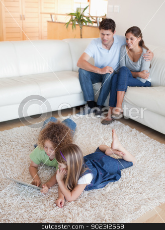Portrait of children using a tablet computer while their happy p stock photo, Portrait of children using a tablet computer while their happy parents are watching in their living room by Wavebreak Media
