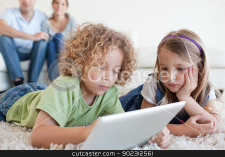 Serious children using a tablet computer while their happy paren stock photo, Serious children using a tablet computer while their happy parents are watching in their living room by Wavebreak Media