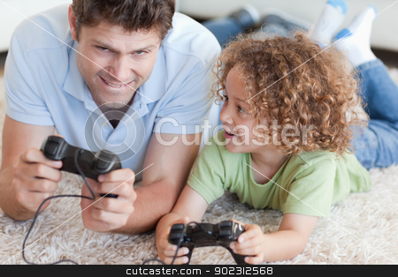Boy and his father playing video games stock photo, Boy and his father playing video games while lying on a carpet by Wavebreak Media