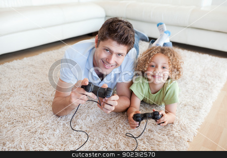 Smiling boy and his father playing video games stock photo, Smiling boy and his father playing video games while lying on a carpet by Wavebreak Media