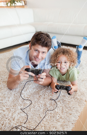 Portrait of a boy and his father playing video games stock photo, Portrait of a boy and his father playing video games while lying on a carpet by Wavebreak Media