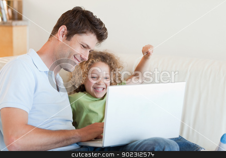 Cheerful boy and his father using a laptop stock photo, Cheerful boy and his father using a laptop in their living room by Wavebreak Media