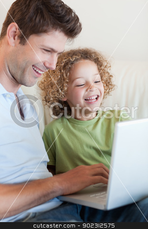 Portrait of a cute boy and his father using a laptop stock photo, Portrait of a cute boy and his father using a laptop in their living room by Wavebreak Media