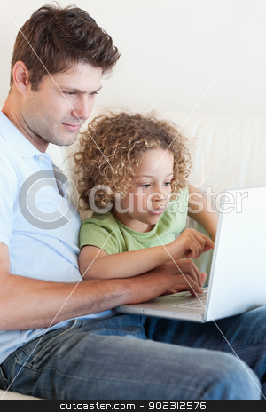 Portrait of a young boy and his father using a laptop stock photo, Portrait of a young boy and his father using a laptop in their living room by Wavebreak Media
