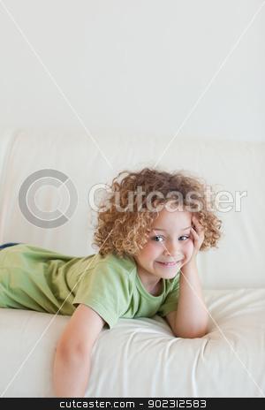 Portrait of a boy lying on a sofa stock photo, Portrait of a boy lying on a sofa while looking at the camera by Wavebreak Media