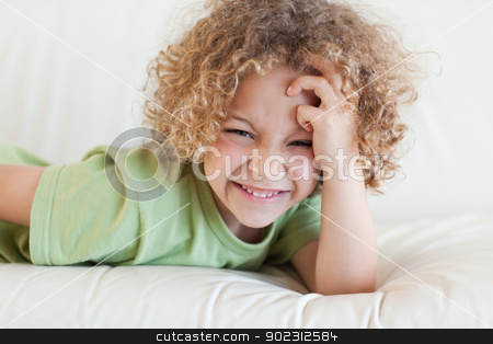 Boy lying on a sofa stock photo, Boy lying on a sofa while looking at the camera by Wavebreak Media