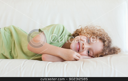 Happy boy lying on a sofa stock photo, Happy boy lying on a sofa while looking at the camera by Wavebreak Media