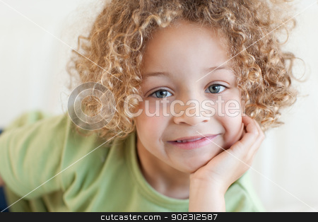 Close up of a cute boy lying on a sofa stock photo, Close up of a cute boy lying on a sofa while looking at the camera by Wavebreak Media