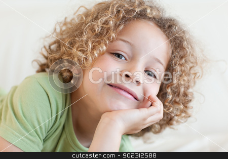 Close up of a smiling boy lying on a sofa stock photo, Close up of a smiling boy lying on a sofa while looking at the camera by Wavebreak Media